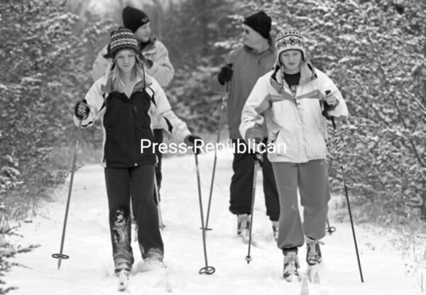 Enjoying the recent snowfall, Plattsburgh residents Cassie Mcelheny (left), 13, and her friend, Kristin Houle, 14, lead the pack during a cross-country skiing expedition Saturday afternoon. Houle's brother and father, Justin and Denis, chat while bringing up the rear at Point au Roche Park. During the summer, the group mountain-bikes throughout the network of trails offered at the park. This is their first time skiing the park this winter.<br><br>(P-R Photo/Gabe Dickens)