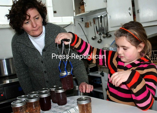 Under the guidance of Cornell Cooperative Extension's Eileen Longware, 7-year-old Kennedy Davis of Ticonderoga learns how to handle canning-jar tongs Sunday as part of a 4-H Extravaganza Day. In addition to learning how to make and preserve jams and jellies, topics included horticulture and gardening, a windmill workshop, how to make lip balm and how to deliver public presentations by Jerry McGovern of the Press-Republican. The event was held at the Essex County Fairgrounds in Westport.<br><br>(Staff Photo/Alvin Reiner)