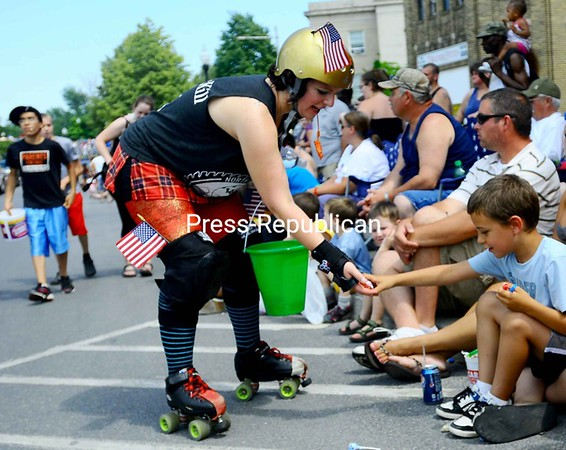 Lumber Jill Erin McGill hands Sawyer Varess, 7 of Plattsburgh candy during Plattsburgh's Fourth of July parade.<br><br>(Staff Photo/Kelli Catana)
