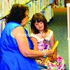 Alexis Brown, 5, picks out books at Plattsburgh Public Library during her first visit there with her great-grandmother, Grace Rascoe. Alexis got a library card and signed up for the summer reading program being held at the library. Studies show children who read over the summer do much better in school than those who don't.<br><br>(Staff Photo/Kelli Catana)
