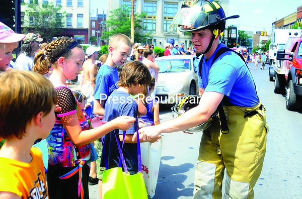 Cumberland Head Firefighter Kyle Murphey wishes everyone a happy Independence day as he walks through the streets of Plattsburgh handing out candy during the parade.<br><br>(Staff Photo/Kelli Catana)