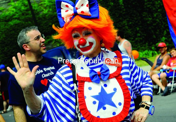 Pipsqueak the clown waves to hundreds of onlookers during Plattsburgh's Fourth of July parade.<br><br>(Staff Photo/Kelli Catana)