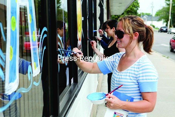 Kelli Gottschall, an employee at the North Country Cultural Center for the Arts, and Afaf Halo, an exchange student at Plattsburgh State from Israel, decorate the windows of Champlain National Bank Wednesday afternoon in preparation for the Mayor's Cup festivities. The center will host artist vendors, crafts for kids and more on the front lawn Saturday and Sunday.<br><br>(P-R Photo/Gabe Dickens)