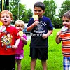 Hunter Goble (left to right), 4, Alexis Gadway, 2, Lucas Gadway, 5, and Quinn Roth, 3, enjoy some cool treats in the shape of various cartoon characters outside of their Plattsburgh home Wednesday afternoon. Unless they're napping, they usually catch the ice cream truck as it passes through the neighborhood from two to three times a week.<br><br>(P-R Photo/Gabe Dickens)