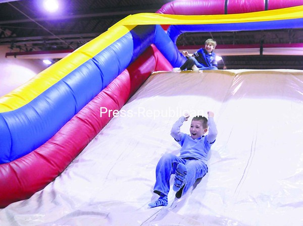Second-grader Tim Gadway slides while fellow second-grader Izaiah Jock waits on top. The inflatable obstacle course was one of the offerings at Beekmantown Central School's recent two-day Winter Wake Up Festival. The health and fitness festival included indoor and outdoor activities, such as snowshoeing, Zumba exercise and an introduction to martial arts.<br><br>(P-R Photo/Andrew Wyatt)