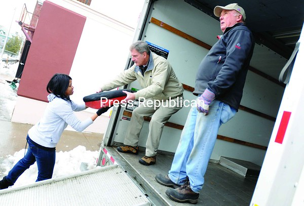 Gertrude Machange, a Plattsburgh State student from Tanzania, helps Rep. Bill Owens load a truck with old theater seats from the Strand Theater in Plattsburgh. Bob Smith (right) of the Plattsburgh Rotary Club assists as well. Owens was on hand Saturday afternoon to help Plattsburgh State students and area Rotarians clean up the inside of the Strand as part of the ongoing renovation project. The student chapter of the Rotary Club, called the Rodaracts, chose the Strand as this year's spring-break service project.<br><br>(P-R Photo/Andrew Wyatt)
