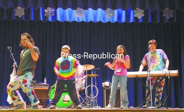 Peru Intermediate School students Mason Maulding (center-left) and Cadyann Douglas dance on stage as the Zucchini Brothers perform. The band, which plays a Rolling Stones-type of music for kids, called this show at the school their 20th-anniversary performance. The first time they played together was in April 1991 at Peru Primary School.<br><br>(P-R Photo/Joanne Kennedy)
