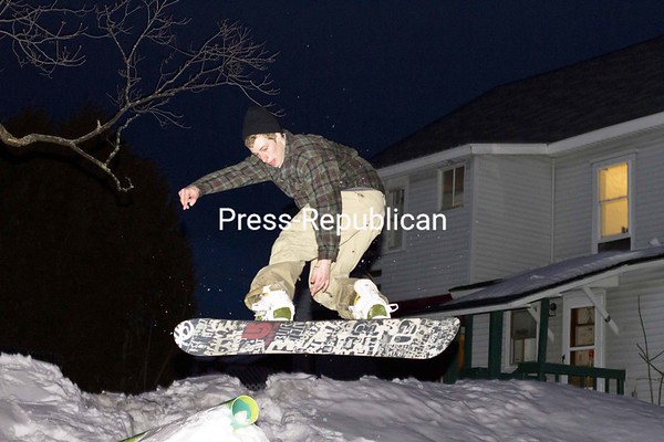 James Heffron performs a board grab in the backyard of his Plattsburgh home Saturday evening. Heffron hasn't had much time lately to use his improvised snowboard park, which consists of a jump leading to a rail made out of PVC pipe. He has been busy with his studies at Plattsburgh State and working at Beartown Ski Area.<br><br>(P-R Photo/Gabe Dickens)