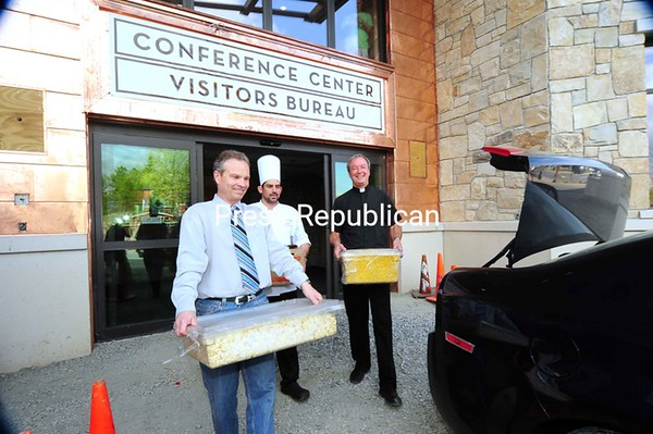 Ted Blazer, president and CEO of the Olympic Regional Development Authority; William Benz, executive chef at the new Lake Placid Conference Center; and the Rev. John Yonkovig, pastor at St. Agnes Parish in Lake Placid, carry excess food from a conference to a car for delivery to flood victims at the Crete Memorial Civic Center in Plattsburgh. About 50 people displaced by recent flooding are staying at the American Red Cross Shelter there.<br><br>(P-R Photo/Jack LaDuke)