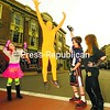 Dressed in a bright-yellow Yellowman suit, Jacob Merrill of Bloomingdale jumps high on Main Street in downtown Saranac Lake Monday as onlookers Ariah Brown (from left), Easton Moore and Brooke Shipman cheer him on. Main Street was blocked off so costumed kids could trick-or-treat safely.<br><br>(P-R Photo/Jack LaDuke)