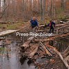 Cindy Kuhn Yourdon of Keeseville (front) and Jean Ryan of Peru use downed logs to cross a section of the trail up Poke-O-Moonshine Mountain flooded by beaver activity. The bridge that had been used to cross the wet area was floating off to the side on the route that follows an old logging road up the mountain. The trailhead is located 1 mile south of the older trailhead, which is 3 miles from Exit 33 off Interstate 87 in Willsboro.<br><br>(P-R Photo/Joanne Kennedy)