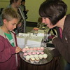 Allie Wemette offers Connor McMinn, 9, from Gabriels, a sample of cupcakes at the North Country Community College craft show. Wemette's business, Simply Cupcakes, and other vendors at the show had a busy day at the recent event.<br><br>(P-R Photo/Joanne Kennedy)