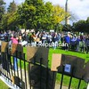 """Cardboard signs supporting the """"99 percent"""" adorn the fence of the Trinity Park memorial as residents share stories of their experiences with fellow demonstrators Saturday at the Occupy Plattsburgh rally in Trinity Park.<br><br>(P-R Photo/Rob Fountain)"""