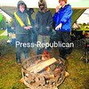 Nick Hammond, Bryan Sullivan and Matthew Adams (from left) of Troop 12, Gabriels, warm themselves by a wood fire after heavy rains flooded their camporee area Saturday at Fort Ticonderoga. Temperatures dropped into the high 30s, causing scout leaders to fear hyperthermia if scouts were not evacuated from the wet and cold area.<br><br>(P-R Photo/Jack LaDuke)