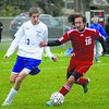 Saranac's Brandon Dutko (16) tries to fend off Peru's Colin Lamica in a Class B semifinal game. The Indians won 2-1 in overtime.<br><br>(Staff Photo/Ryan Hayner)