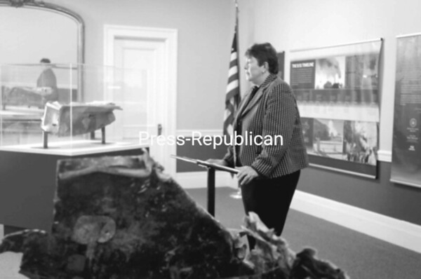 "New York's Deputy Secretary of State Dierdre ""Dede"" Scozzafava stands between a crushed file cabinet from the World Trade Center and a twisted piece of the lightweight aluminum that surrounded the World Trade Center buildings. Scozzafava came to Plattsburgh to unveil the New York Remembers exhibit at Plattsburgh City Hall.<br><br>(Staff Photo/Kelli Catana)"