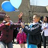 Plattsburgh State student Maggie Edwards (left) cuts loose the last of the balloons held by Dave Jones, 9, of Peru, to commemorate friends and family members lost to suicide during the annual Out of the Darkness Campus Walk Saturday afternoon. Sponsored by the American Foundation for Suicide Prevention, the event featured guest speakers, Zumba, a musical performance by Minor Adjustments and information on how to help spot someone at risk for suicide. Help is available 24 hours a day by calling the National Suicide Prevention Hotline at 800-273-TALK (8255).<br><br>(P-R Photo/Gabe Dickens)