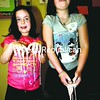 Anya Kazmierczak (left) and Megan Quinn let a non-Newtonian fluid in suspension called oobleck drip from their hands as they stand in a tub of the goo during Keene Central School's recent Super Scientific Science Slam. <br><br>(Staff Photo/Alvin Reiner)