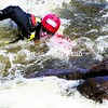 Firefighter Joe Gordon, a member of the Morrisonville Fire Department, uses an eddy, which is an area of swirling water and a reversal in current caused by an obstruction in whitewater — in this case a large boulder — to swim upstream and grab hold of the rock during a training day hosted by the Adirondack Regional Technical Rescue Task Force.<br><br>(P-R Photo/Gabe Dickens)