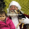 """Santa receives a kiss from """"Chopper"""", a Chihuahua, with Elliot Muller on his lap, during Santa Pet Photo Day at Tails of the Adirondacks in Plattsburgh on Saturday. All proceeds go to benefit the Adirondack Humane Society and to help spay/neuter animals. If your pet missed this chance to visit Santa you'll get another chance Dec. 8 from 10 a.m. to 4 p.m.<br><br>(P-R PHOTO/ROB FOUNTAIN)"""