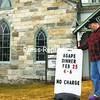 The Rev. Leon Hebrink of the Westport Federated Church places a sign advertising the agape dinner to be held from 4 to 6 p.m. Saturday. He expressed thanks to contributors, especially Juniper Hill Farm and the Dogwood Bakery.<br><br>(Staff Photo/Alvin Reiner)