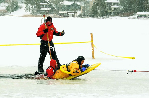 About a dozen firefighters from Saranac Lake, Lake Placid and several other towns took part in an ice-rescue drill on Pontiac Bay in Saranac Lake on Sunday. Here, Sam Anderson (left) has successfully attached Brad Zambri to a rescue sled that is being pulled ashore by a land crew. Officials warn the public to know the thickness of the ice before venturing out on it and to exercise caution at all times. <br><br>(P-R Photo/Jack LaDuke)