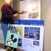 Julie Dowd, a docent at the Clinton County Historical Museum, installs a display on the Cold War in the lobby at Clinton County Government Center, as a teaser about the full exhibit at the museum. That one, which has been up for two years, will be replaced with a new installation in the near future.<br><br>(Staff Photo/Kelli Catana)
