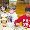 Sophie Kabeli (from left), 5, Max Grafstein, 6, and Isaac Nizel, 6, use several ingredients to create the Jewish Passover seder dish charoset, which represents the mortar the Israelites used to construct the pyramids of Egypt during their enslavement, recetnly at Temple Beth Israel in Plattsburgh. Throughout the years, many countries have included their own items in the sweet, dark-colored dish, but the traditional recipe calls for honey, cinnamon, apples, grape juice and walnuts.<br><br>(P-R Photo/Gabe Dickens)