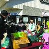 Greg Roberts of Champlain (left) buys cookies from Girl Scout Troop 4262 outside Stewart's Shop in Rouses Point. Tending the outdoor sale table are (from left), Debbie Jolicoeur, Troop Leader Kenna Dumas, Gracie Dumas, Hope Jolicoeur, and, with a T-shirt tote bag over her arm, Sadie Dumas.<br><br>(Staff Photo/Suzanne Moore)