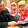 Heather Carter helps her twin daughters Fiona (left) and Violet, 2, pick out a book at the Journey into Reading event held at Champlain Centre mall in Plattsburgh. Anyone under the age of 18 can pick up a free book between 4:30 and 6:30 p.m. Thursdays.<br><br>(Staff Photo/Kelli Catana)