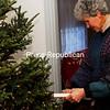 Geri Rickert adorns this Christmas tree with gold garlands.<br><br>(Staff Photo/Robin Caudell)