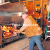 Dick Atwood fills his wood-fired evaporator, which reduces sap into syrup.<br><br>(Staff Photos/Kelli Catana)