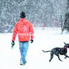 Junior James Murnane, a history major at SUNY Plattsburgh, takes his pitbull-Labrador-retriever-mix puppy, Jaxx, for a walk along the Saranac River Trail as heavy, wet snow falls behind Memorial Hall. The National Weather Service forecast was for 3 to 6 slushy inches for eastern Clinton and Essex counties, with anticipated accumulations of 5 to 10 for western Clinton and Essex through the early morning today.<br><br>(P-R Photo/Gabe Dickens)
