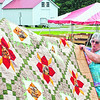 Essex County Fair Secretary Bertha Rand displays a quilt donated as a fundraiser for this year's fair. The quilt was created by Tina Westover of Hudson Falls, and tickets are $1 each. The fair starts Wednesday morning, and vendors are setting up now.<br><br>(STAFF PHOTO/LOHR McKINSTRY)