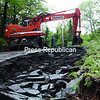 The Town of Dannemora Highway Department works on filling in damage done to Hugh Herron Road by Tuesday's flooding. Highway Superintendent Mark Siskavich said that 4 to 5 feet of water was flowing down the road and across Route 374, which, coupled with the damage done to the opposite end of Hugh Herron Road in the Town of Saranac, had stranded residents living on the road for several hours while crews worked to get one lane open.<br><br>(P-R PHOTO/GABE DICKENS)