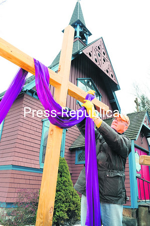 On Holy Thursday, Tom Dudones, a parishioner at St. Luke Episcopal Church in Saranac Lake, drapes the central of three crosses in purple, representing repentance. For today, Good Friday, and Holy Saturday, the crosses in front of the oldest house of worship in the mountain village will be shrouded in black, representing the crucifixion of Christ. And on Easter Sunday, white will celebrate Christ's resurrection.<br><br>(P-R PHOTO/JACK LADUKE)