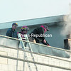 Firefighters use an axe to chop through the tin roof recently installed at the Hope Community Center in Brushton to find the source of the fire that broke out there.<br><br>(Staff Photo/Denise Raymo)