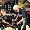 Samantha Warre, 7, of Dannemora, learns something about the craft of iron work from Richard Banker of Paul Smith's Saturday at the second annual Adirondack Rural Skills and Homestead Festival held at the Paul Smith's Visitors Center. Banker must heat the metal to 2,500 degrees before he can pound it into an artistic object. He has been a blacksmith for 39 years. A crowd of more than 1,200 attended the day-long event. A number of homesteading skills were demonstrated at the festival.<br><br>(P-R PHOTO/JACK LADUKE)