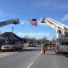 A flag suspended between two aerial fire trucks pays tribute to the late Russell Trombly as the Chazy man's funeral cortege passes beneath it Wednesday morning on Route 9 north of the City of Plattsburgh. Trombly was Clinton County sheriff from 1977 until his retirement in 1999. <br><br>(SUZANNE MOORE/STAFF PHOTO)