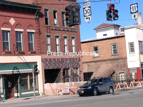 """The building to the left of the bridge, with the """"sidewalk closed"""" sign in front, is 395 West Main St. in Malone, which has been deemed ready to collapse. A state of emergency was declared Wednesday by Village Mayor Todd LePine, and plans are under way to try to take the structure down safely.<br><br>(DENISE A. RAYMO/STAFF PHOTO)"""
