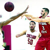 Plattsburgh State's Mike Mitchell passes the ball off to a teammate past Cortland's Lamard Herron during Saturday's SUNYAC men's basketball game at Memorial Hall in Plattsburgh.<br><br>(GABE DICKENS/P-R PHOTO)