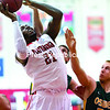Plattsburgh State's Reggie Williams puts in a basket after a rebound against a pair of Oswego defenders during Friday's SUNYAC men's basketball game at Memorial Hall in Plattsburgh.<br><br>(GABE DICKENS/P-R PHOTO)