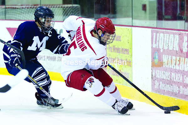 Plattsburgh State's Kevin Emmerling picks up a loose puck behind the opponent's net while Middlebury's Zach Weier gives chase during Friday's nonconference men's hockey game at the Ronald B. Stafford Arena in Plattsburgh.<br><br>(GABE DICKENS/P-R PHOTO)