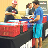 An Ironman Lake Placid volunteer helps Matt Toporowski (left) of Manhattan check in Friday at the Olympic Center. Today's race will be Toporowski's first full-distance Ironman. (Courtney Lewis/Staff Photo)