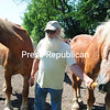 Farm Manager George Weidle offers corn to two of the 15 horses on the property. (ROB FOUNTAIN/STAFF PHOTO)