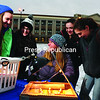 During the recent Green Shindig at Lake Placid Central School, Kerri Ziemann (center), of the Wild Center in Tupper Lake, demonstrates how to make solar snacks in a pizza box, using the sun as a heating source. Sabrina Ciamber (from left), 15; Laure Frank, 15; Madeline Frank,15; and Dakota Breglia,15; all of Gouverneur High School, look on. Other demonstrations included a bicycle-powered blender for making smoothies and other climate changing displays. About 75 people attended the event on the Speed Skating Oval.<br><br>(JACK LADUKE/P-R PHOTO)