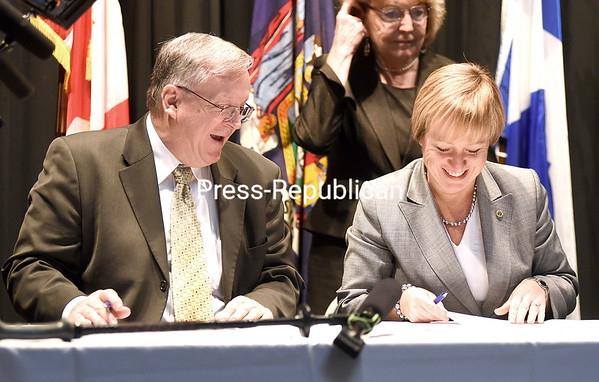 Plattsburgh Mayor James Calnon and Longueuil, Quebec, Mayor Caroline St-Hilaire share a laugh as they sign a Declaration of Cooperation Monday during the Rendezvous Longueuil-Plattsburgh luncheon at City Hall auditorium. (ROB FOUNTAIN/STAFF PHOTO)