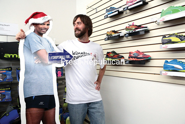 Jeremy Drowne, co-owner of Kinetic Running in Plattsburgh, strikes a whimsical pose with Meb Keflezighi, an Eritrean-born American who won silver in the 2004 Olympic marathon and took first place in the 2014 Boston Marathon. Drowne is looking forward to Small Business Saturday, a new experience, since his shop opened just this year.  (GABE DICKENS/P-R PHOTO)