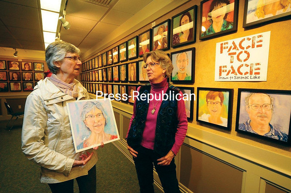 """Artist Diane Leifheit of Saranac Lake (right) stands in the Cantwell Room of the Saranac Lake Free Library chatting with Karen Baker, who holds the portrait Leifheit made of her. It is one of nearly 200 portraits the artist completed of local residents over the past year. She began her """"Face to Face"""" project in 2014 at Compass Printing on Main Street in downtown Saranac Lake. It was a convenient location to drop in for a two-hour sitting for a portrait, done in pastels and at no cost to Leifheit's subjects. In the background are the walls of the library, nearly covered with the many 1-foot-square portraits she completed. Each person will receive a full-sized portrait digital print of their image as a gift from the artist. The show will be on display through Monday, Dec. 7. Baker said that she was so proud of her painting that she put it on Facebook for everyone to see. (JACK LADUKE/P-R PHOTO)"""