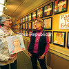 "Artist Diane Leifheit of Saranac Lake (right) stands in the Cantwell Room of the Saranac Lake Free Library chatting with Karen Baker, who holds the portrait Leifheit made of her. It is one of nearly 200 portraits the artist completed of local residents over the past year. She began her ""Face to Face"" project in 2014 at Compass Printing on Main Street in downtown Saranac Lake. It was a convenient location to drop in for a two-hour sitting for a portrait, done in pastels and at no cost to Leifheit's subjects. In the background are the walls of the library, nearly covered with the many 1-foot-square portraits she completed. Each person will receive a full-sized portrait digital print of their image as a gift from the artist. The show will be on display through Monday, Dec. 7. Baker said that she was so proud of her painting that she put it on Facebook for everyone to see. (JACK LADUKE/P-R PHOTO)"